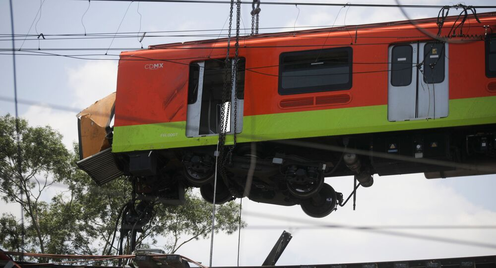 Workers move a train car from a site where an overpass for a metro partially collapsed with train cars on it at Olivos station in Mexico City, Mexico May 4, 2021