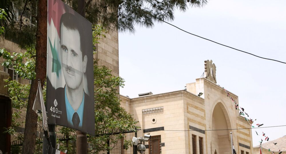 A picture of Syria's President Bashar al-Assad is pictured outside the parliament building in Damascus, Syria April 18, 2021.