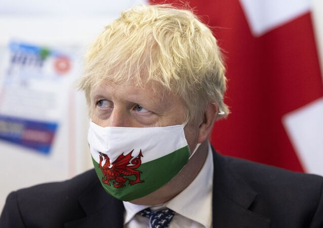 British Prime Minister Boris Johnson wears a Welsh flag face mask as he visits Marco's cafe in Barry Island during the Senedd election campaign on 3 May 2021 in Barry, south Wales