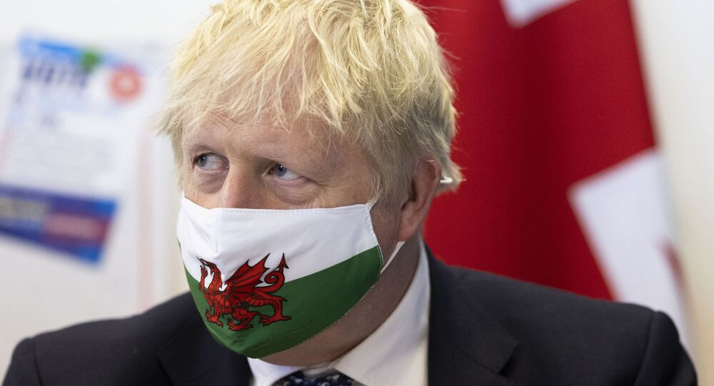 British Prime Minister Boris Johnson wears a Welsh flag face mask as he visits Marco's cafe in Barry Island during the Senedd election campaign on May 3, 2021 in Barry, south Wales