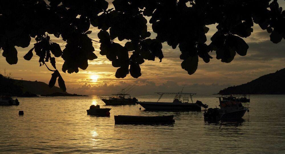FILE - In this Friday, March 1, 2019 file photo, the sun sets over a small bay with fishing and pleasure crafts at anchor, on Mahe island, Seychelles.
