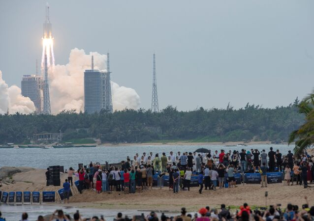 People watch from a beach as the Long March-5B Y2 rocket, carrying the core module of China's space station Tianhe, takes off from Wenchang Space Launch Center in Hainan province, China April 29, 2021.