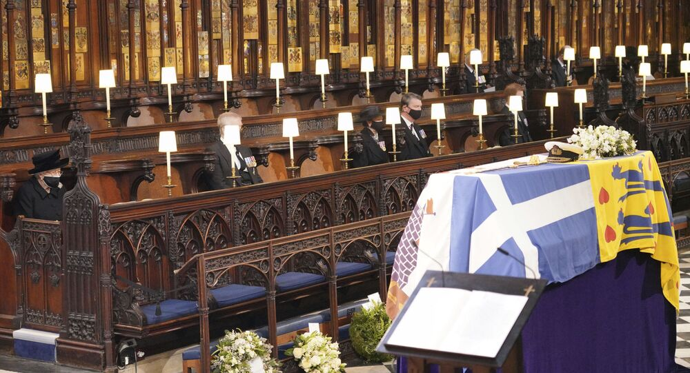 Britain's Queen Elizabeth II, left, Prince Andrew, Princess Anne the Princess Royal and Vice Admiral Timothy Laurence, right, look on the flag draped coffin in St. George's Chapel during the funeral of Prince Philip, the man who had been by the Queen's side for 73 years, at Windsor Castle, Windsor, England, Saturday April 17, 2021. Prince Philip died April 9 at the age of 99 after 73 years of marriage to Britain's Queen Elizabeth II.