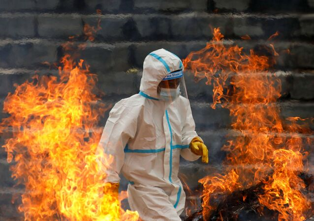 A man wearing personal protective equipment (PPE) walks past the fire as he cremates the bodies of people who died due to coronavirus disease (COVID-19), as India's outbreak spreads across South Asia, in Kathmandu, Nepal May 5, 2021.