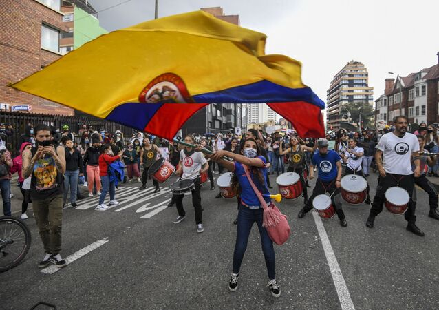 A woman waves a Colombian national flag during a protest against a tax reform proposed by Colombian President Ivan Duque's government in Bogota, on 4 May 2021. The international community on Tuesday decried what the UN described as an excessive use of force by security officers in Colombia after official data showed 19 people killed and 846 injured during anti-government protests.