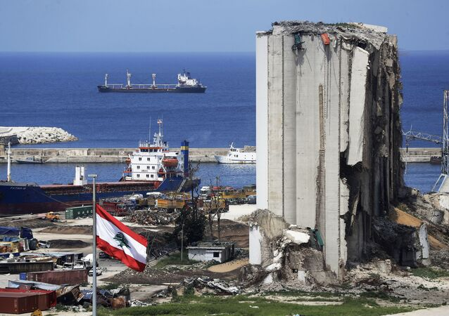 A picture shows a view of the damaged grain silos at the port of the Lebanese capital Beirut, on April 9, 2021, still reeling from the destruction due to a catastrophic blast in a harbour storage unit last August that killed more than 200 people and damaged swathes of the capital, with the Togo-flagged Fatima M bulk carrier ship moored nearby.