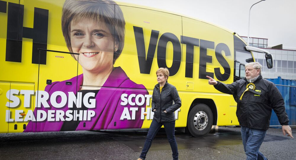 Scotland's First Minister and leader of the Scottish National Party (SNP), Nicola Sturgeon (R) walks past the campaign battle bus with SNP candidate Angus Robertson during a campaign visit to LOVE Gorgie Farm in Edinburgh, Scotland on May 4, 2021, ahead of the upcoming Scottish Parliament election which is to be held on May 6, 2021.