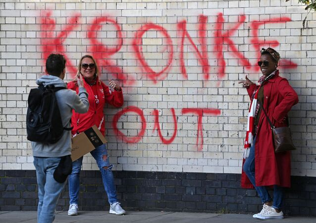 Two fans have their photograph taken beside a Kronke Out message sprayed on a wall as supporters protest against Arsenal's US owner Stan Kroenke, outside English Premier League club Arsenal's Emirates stadium in London on 23 April 2021, ahead of their game against Everton.