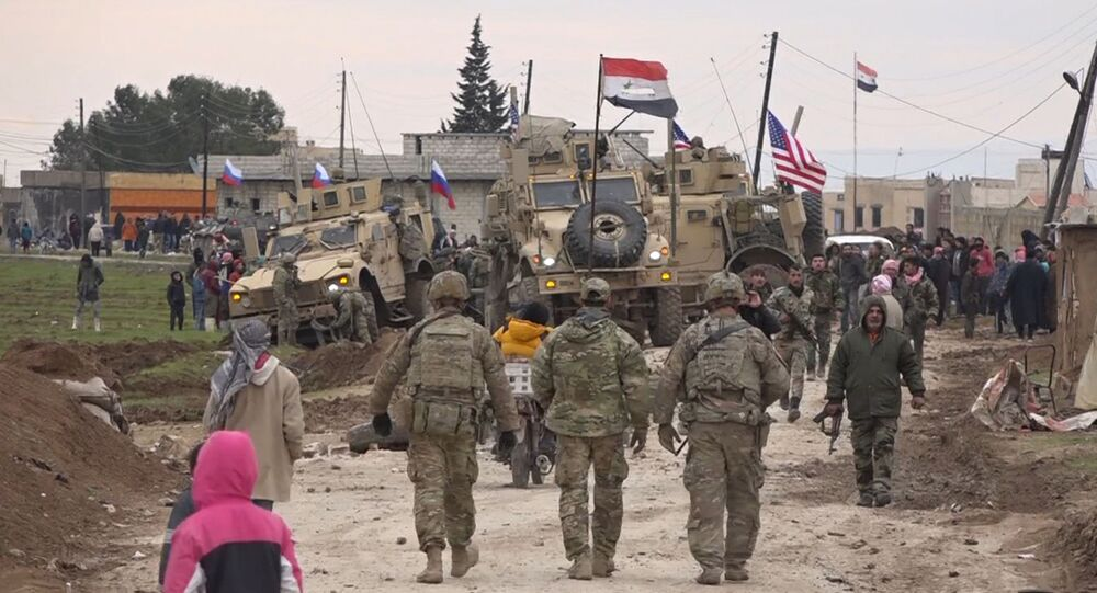 In this frame grab from a video, Russians, Syrians and others gather next to an American military convoy stuck in the village of Khirbet Ammu, east of Qamishli city, Syria, 12, February 2020. Syria's official news agency SANA said that locals had gathered at an army checkpoint, pelting the U.S. convoy with stones and taking down a US flag flying on a vehicle when troops fired with live ammunition and smoke bombs. (AP Photo)