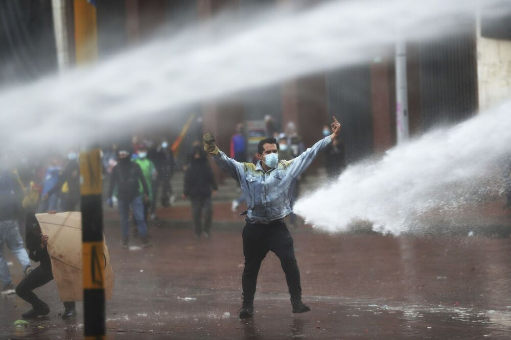 A demonstrator gestures at a police water cannon during an anti-government protest in Bogota, Colombia, Wednesday, May 2021.