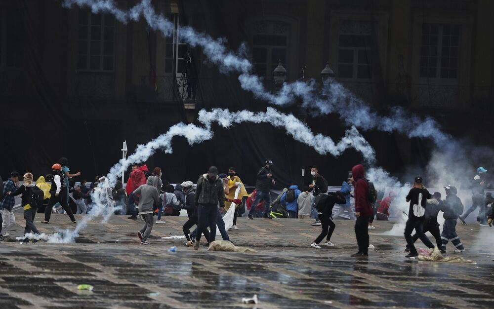 Anti-government protesters throw tear gas canisters back at the police during clashes in Bogota, Colombia, Wednesday, 5 May 2021.