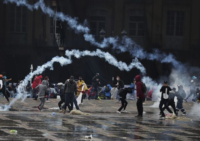 Anti-government protesters return tear gas canisters at the police during clashes in Bogota, Colombia, Wednesday, 5 May 2021.
