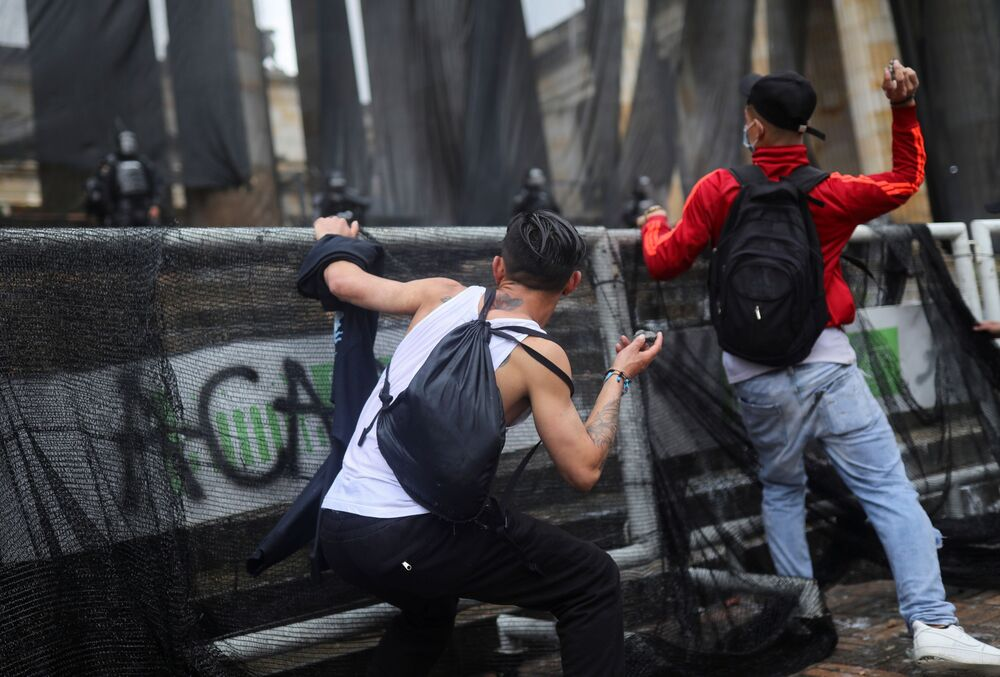 Demonstrators prepare to throw stones during a protest against poverty and police violence in Bogota, Colombia, 5 May 2021.