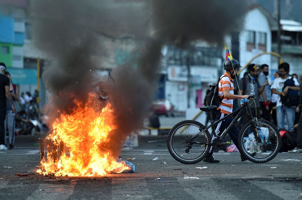 A demostrator walks past a burning barricade blocking a street during a protest against President Ivan Duque's government in Cali, Colombia on 5 May 2021.