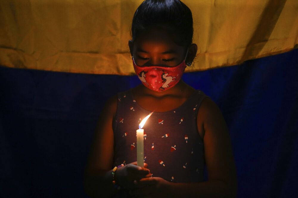 A Colombian girl residing in Panama holds a lit candle during a protest against Colombian President Ivan Duque's government in support of protests taking place in her country, at Urraca Park in Panama City, on 5 May 2021.