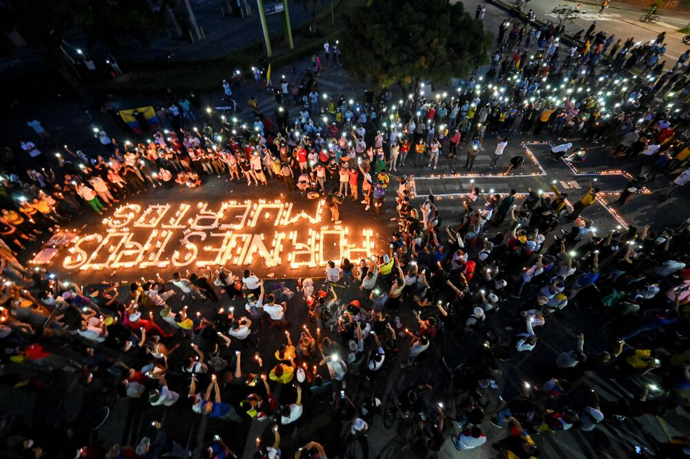 People gather around candles and words on the pavement reading for our dead during a vigil on 5 May 2021 in Cali, Colombia, in honor of the demonstrators who died during protests against the government of President Ivan Duque.