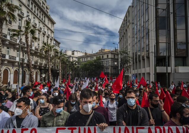 Demonstrators wearing protective face masks against the coronavirus, Covid-19, and members of the Greek Labour Union (PAME) protest during a strike against the new Labour law, in central Athens on May 6, 2021.