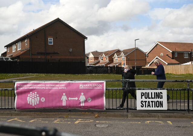 People walk past banners for a polling station in Hartlepool, County Durham on 6 May 2021, as voters cast their ballots in local elections.