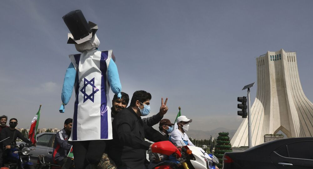 A demonstrator on a motorcycle holds an effigy representing Israel and the United States  during the annual Al-Quds, or Jerusalem, Day rally, with the Azadi (Freedom) monument tower seen at right, in Tehran, Iran, Friday, 7 May 2021.