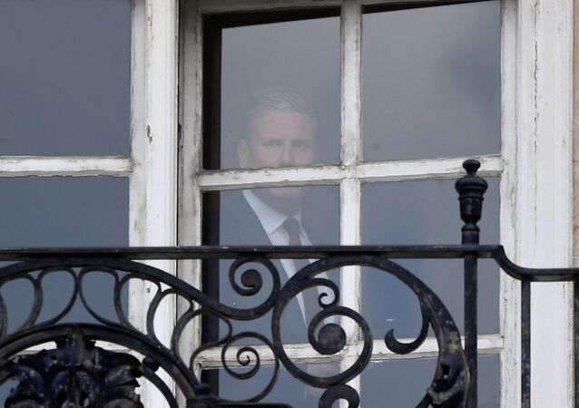 Britain's Labour Party leader Keir Starmer is seen in the window of his offices in London, Britain, May 7, 2021. REUTERS/Toby Melville