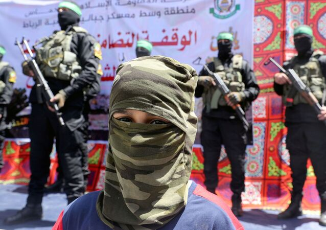 A masked Palestinian boy looks on as Hamas militant take part in a protest over the possible eviction of several Palestinian families from homes on land claimed by Jewish settlers in the Jerusalem's Sheikh Jarrah neighbourhood, in the northern Gaza Strip on May 7, 2021.