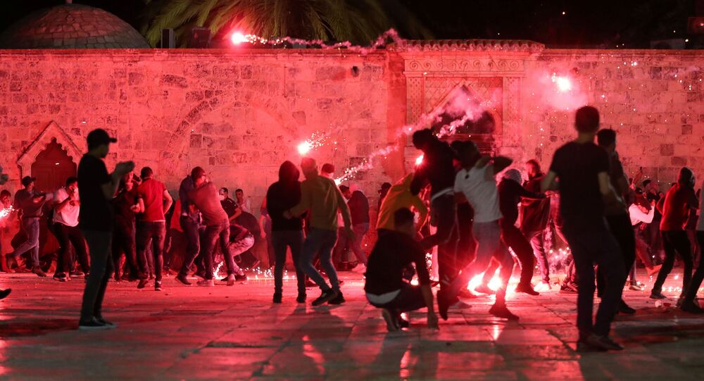 Palestinians react as Israeli police fire stun grenades during clashes at the compound that houses Al-Aqsa Mosque, known to Muslims as Noble Sanctuary and to Jews as Temple Mount, amid tension over the possible eviction of several Palestinian families from homes on land claimed by Jewish settlers in the Sheikh Jarrah neighbourhood, in Jerusalem's Old City, May 7, 2021