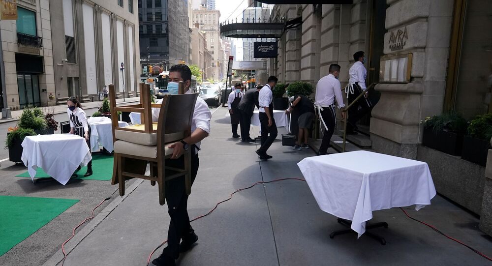 FILE PHOTO: A waiter sets up tables in front of a restaurant on a street on the first day of the phase two re-opening of businesses following the outbreak of the coronavirus disease (COVID-19), in the Manhattan borough of New York City, New York, U.S., June 22, 2020.