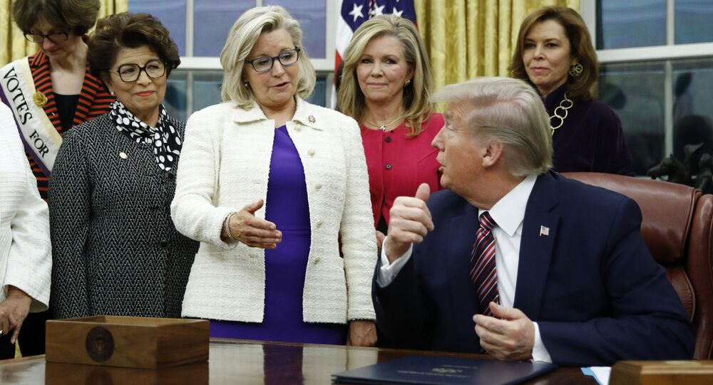 Rep. Liz Cheney, R-Wyo., center, speaks with President Donald Trump during a bill signing ceremony for the Women's Suffrage Centennial Commemorative Coin Act in the Oval Office of the White House, Monday, Nov. 25, 2019, in Washington.