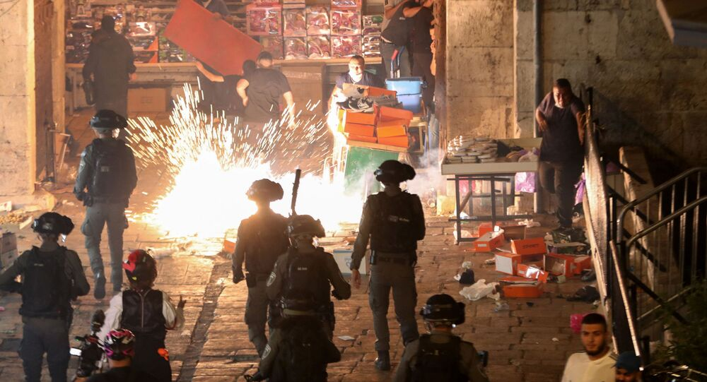 Palestinians react as Israeli police fire a stun grenade during clashes at Damascus Gate on Laylat al-Qadr during the holy month of Ramadan, in Jerusalem's Old City, May 9, 2021