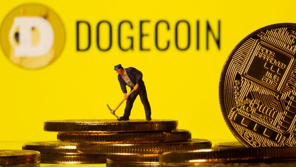 A small toy figure is seen on the cryptocurrency representation with Dogecoin logo in the background in this illustration picture taken, April 20, 2021 - Sputnik International