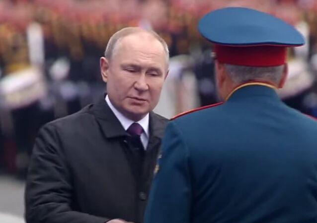 The defence minister has completed his inspection, and heads for the central tribune to report to Russian President Vladimir Putin, Commander-in-Chief of Russia's armed forces.