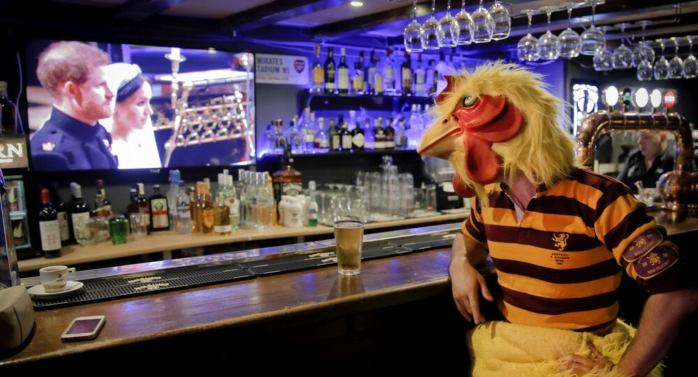 Colin Liddell, wearing a chicken outfit, watches the royal wedding of Meghan Markle and Prince Harry of Wales, at the Mojo Bar in Bucharest, Romania, Saturday, 19 May 2018