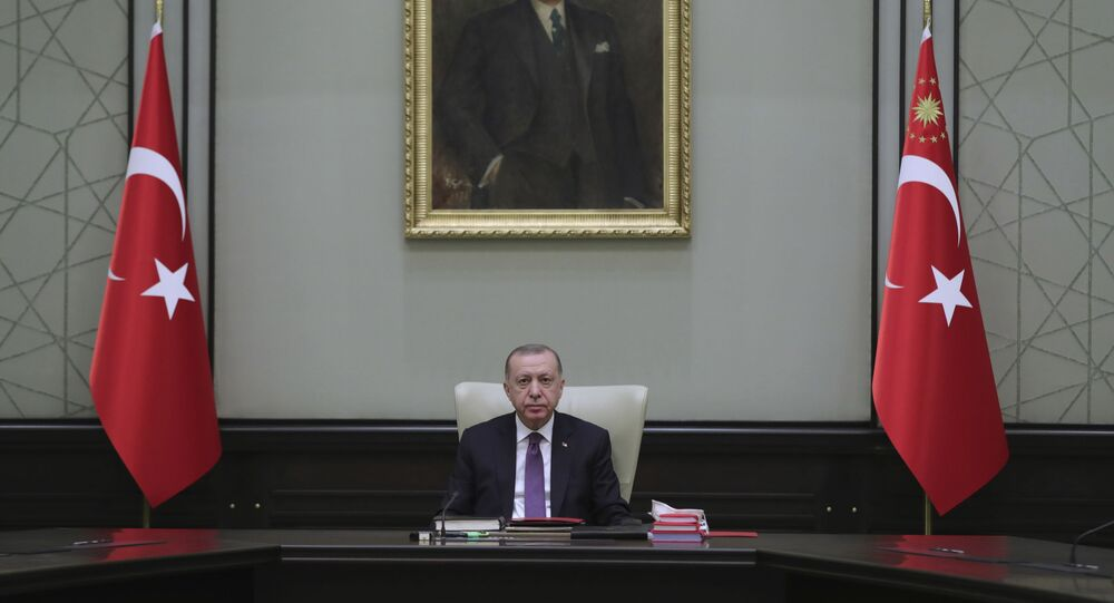 Turkey's President Recep Tayyip Erdogan, backdropped by a painting depicting modern Turkey's founder Mustafa Kemal Ataturk, chairs his government's cabinet in Ankara, Turkey, Monday, April 26, 2021.