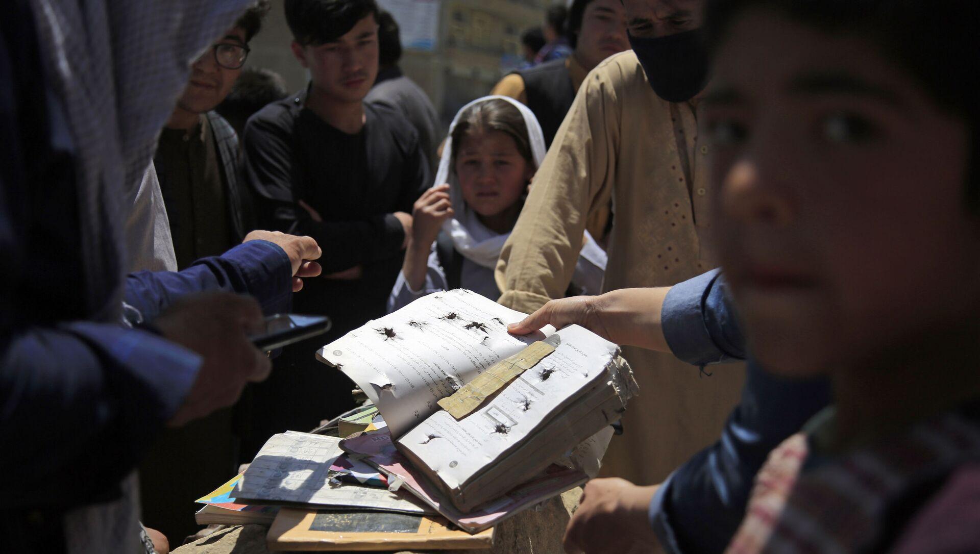 Afghans go through belongings left behind after deadly bombings on Saturday near a school in Kabul, Afghanistan, 9 May 2021.  - Sputnik International, 1920, 26.07.2021