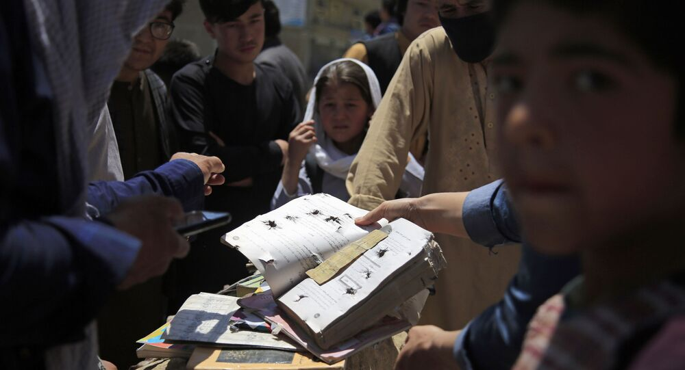 Afghans go through belongings left behind after deadly bombings on Saturday near a school in Kabul, Afghanistan, Sunday, May 9, 2021.