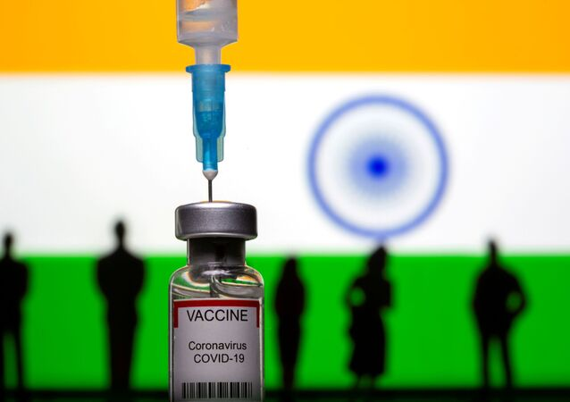 3D-printed small toy figurines, a syringe and vial labelled coronavirus disease (COVID-19) vaccine are seen in front of India flag