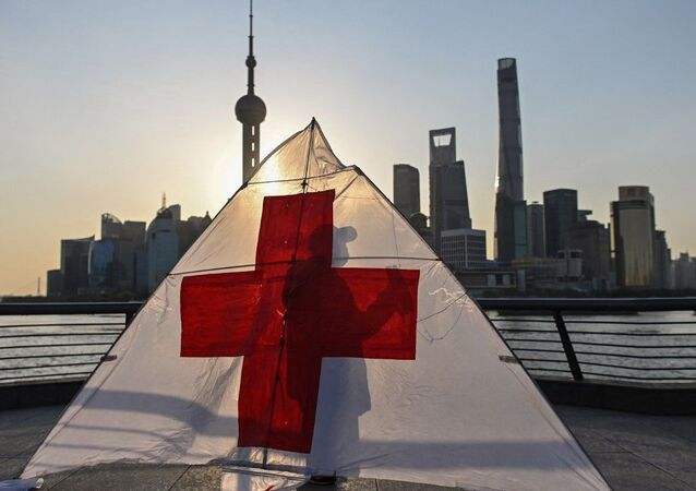 This picture taken on March 23, 2020 shows Gu, 80, wearing a facemask as a preventive measure against the spread of the COVID-19 novel coronavirus, as he prepares to fly his kite in the early morning on the promenade of the Bund along Huangpu River in Shanghai.