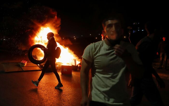 A Palestinian woman demonstrator carries a tire as she walks past a burning barricade during an anti-Israel protest over tension in Jerusalem, near the Jewish settlement of Beit El near Ramallah, in the Israeli-occupied West Bank May 9, 2021