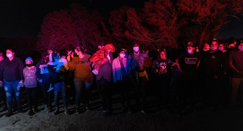 Asylum-seeking migrant families wait to be escorted by the U.S. Border Patrol after crossing the Rio Grande river into the United States from Mexico, in Roma, Texas, U.S., May 7, 2021