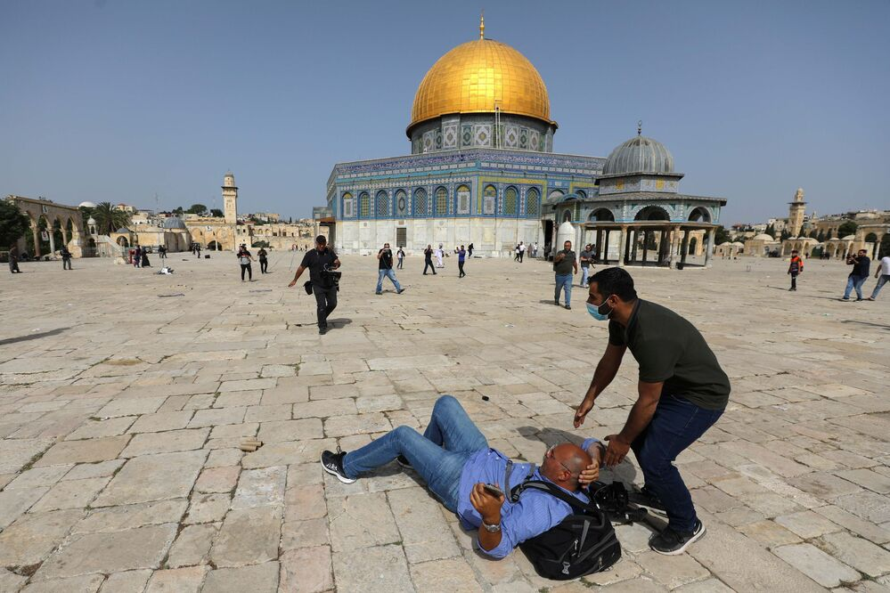 A cameraman is helped by a Palestinian after falling to the ground during clashes with Israeli police at the compound that houses the Al-Aqsa Mosque, known to Muslims as the Noble Sanctuary and to Jews as the Temple Mount, in Jerusalem's Old City, 10 May 2021.