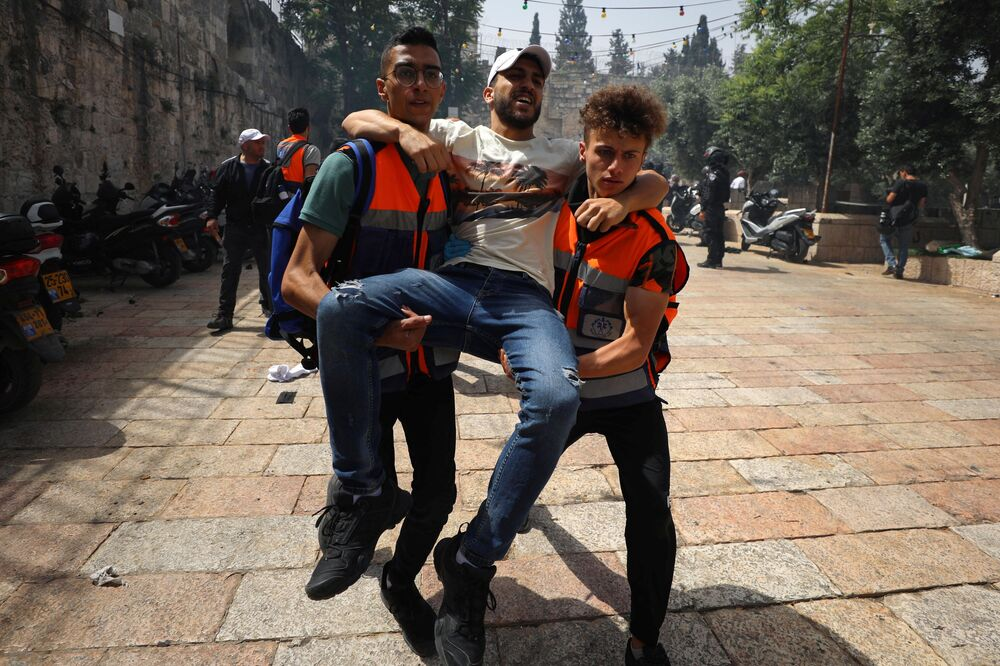 A wounded Palestinian is evacuated during clashes with Israeli police at the compound that houses Al-Aqsa Mosque, known to Muslims as Noble Sanctuary and to Jews as Temple Mount, in Jerusalem's Old City, May 10, 2021.