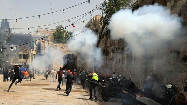 Palestinians run away as Israeli police fire a stun grenade during clashes at the compound that houses Al-Aqsa Mosque, known to Muslims as Noble Sanctuary and to Jews as Temple Mount, in Jerusalem's Old City, May 10, 2021.  - Sputnik International