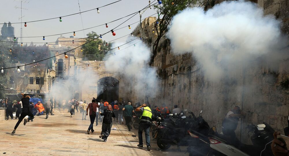 Palestinians run away as Israeli police fire a stun grenade during clashes at the compound that houses Al-Aqsa Mosque, known to Muslims as Noble Sanctuary and to Jews as Temple Mount, in Jerusalem's Old City, May 10, 2021.
