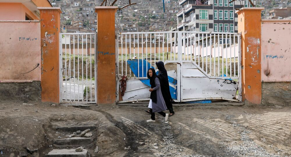 A woman with a girl walks past the site of a car bomb blast that targeted schoolgirls in Kabul, Afghanistan May 10, 2021.