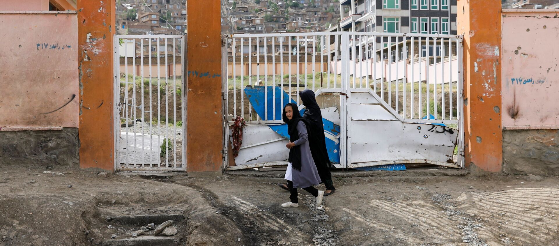 A woman with a girl walks past the site of a car bomb blast that targeted schoolgirls in Kabul, Afghanistan May 10, 2021.  - Sputnik International, 1920, 19.05.2021