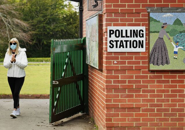 A woman arrives at a polling station set up at a bowls pavillion in a park in Hartlepool to cast a vote in local elections on May 6, 2021
