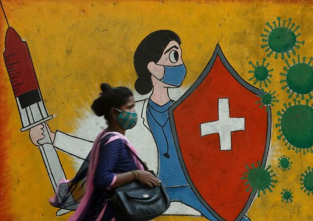 A woman walks past a graffiti on a street, amidst the spread of the coronavirus disease (COVID-19) in Mumbai, India, May 10, 2021