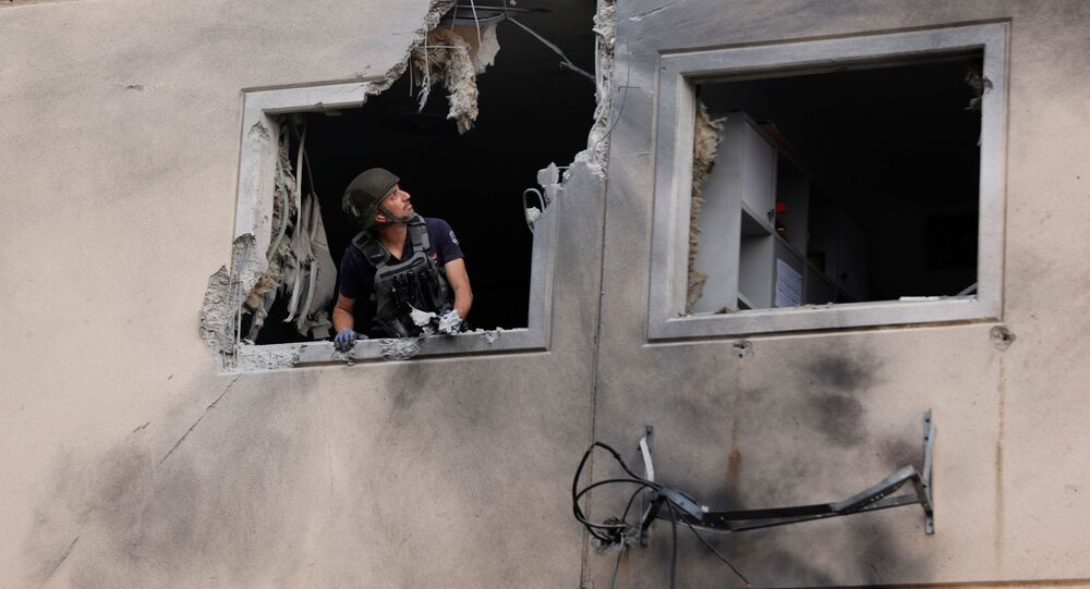 An Israeli police bomb disposal expert looks out from the window of a residential building that was damaged after it was hit by a rocket launched from the Gaza Strip, in Ashkelon, southern Israel May 11, 2021.