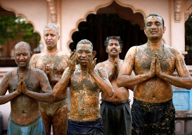 People pray after applying cow dung on their bodies during cow dung therapy, believing it will boost their immunity to defend against the coronavirus disease (COVID-19) at the Shree Swaminarayan Gurukul Vishwavidya Pratishthanam Gaushala or cow shelter on the outskirts of Ahmedabad, India, May 9, 2021