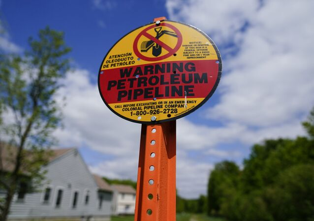 A warning sign is posted along the path of the Colonial Pipeline in Garnet Valley, Pa., Monday, May 10, 2021. Gasoline futures are ticking higher following a cyberextortion attempt on the Colonial Pipeline, a vital U.S. pipeline that carries fuel from the Gulf Coast to the Northeast.